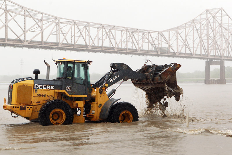 A worker clears mud and debris from a flooded street near the Martin Luther King Bridge in St. Louis in early May as flooding has been a problem all spring.