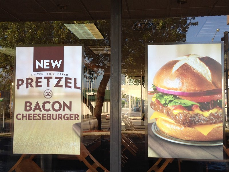 A pretzel bacon burger is pictured in a promotional sign in the window of a Wendy's restaurant.