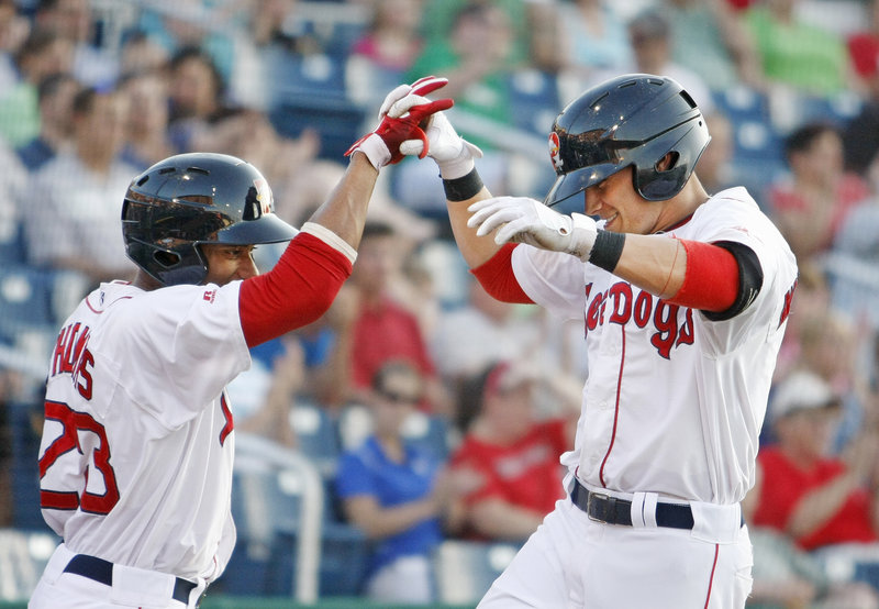 Tony Thomas, left, high-fives teammate Shannon Wilkerson, whose fifth-inning home run provided the Sea Dogs a cushion en route to a victory Friday night over the Altoona Curve at Hadlock Field.