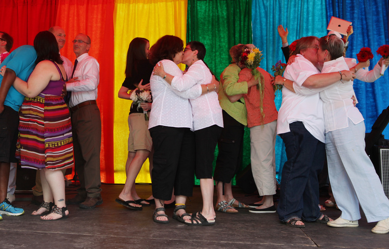 Newly married couples kiss following a mass wedding held Saturday in Deering Oaks Park in Portland as part of the Pride Parade and festival.