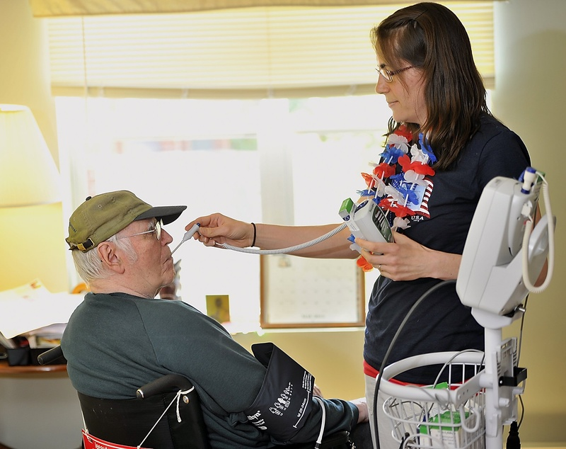Nikki Rollins, a certified nurse assistant, takes the temperature and blood pressure of a resident at the Mid Coast Senior Health Center in Brunswick last month. The House has passed some changes to the 2011 health-care reform law, but by slim margins that wouldn't stand up to a veto by the governor.