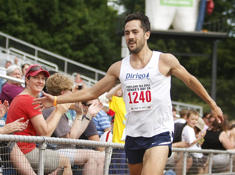 Robert Gomez of Saco gets hand-slap congratulations from the crowd along the finish at Hadlock Field. Gomez won the race with an official chip time of 15 minutes, 19 seconds.
