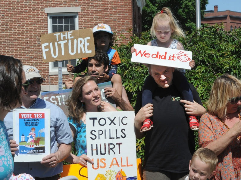 Two-year-old Cadence Kessler of South Portland sits atop her dad Chris Kessler, who stands next to her mother, Jessie Kessler, left, as they join members of the Concerned Citizens of South Portland at a news conference Monday. TarSands