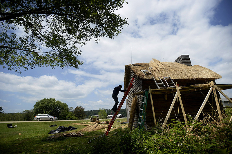 Colin McGhee, originally from England, says the thatched roof he's installing on this replica building at Colonial Pemaquid should last 40 years.