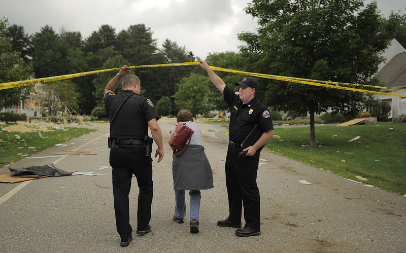 Dee Dyer-Reich ducks under police tape at Gables Drive in Yarmouth Wednesday, as she goes to retrieve medication from her father's condo that was damaged in the Tuesday blast.