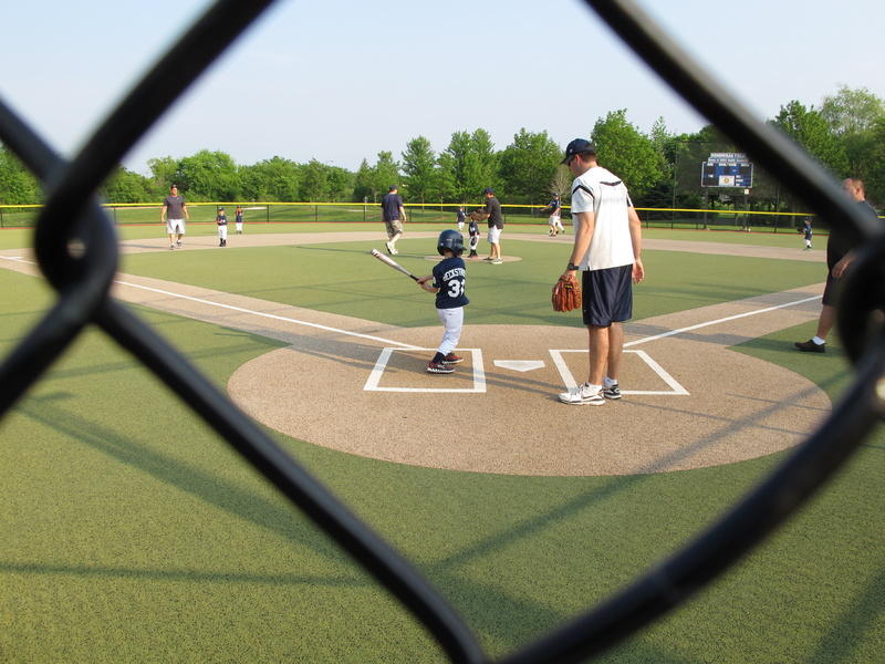A young batter takes a swing as a father who is a coach supervises at a youth baseball game in Buffalo Grove, Ill., on Monday. Earlier in the month, park district officials in the Chicago suburb posted signs asking parents to behave and keep the games in perspective.