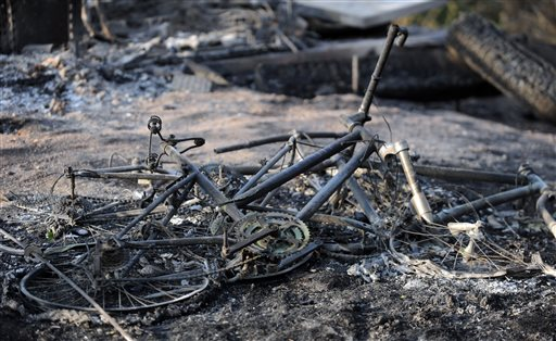 The remains of a mountain bike lays in the ashes outside a house along Holmes Road Thursday, June 13, during the third day of the Black Forest Fire north of Colorado Springs, Colo.(AP Photo/The Gazette, Christian Murdock) murdock;fire black forest;slurry bomber