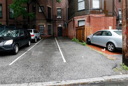 Parking spaces behind 298 Commonwealth Ave. in Boston are seen Friday. The two open spaces at right, front and back, were sold at auction on Thursday for $560,000.