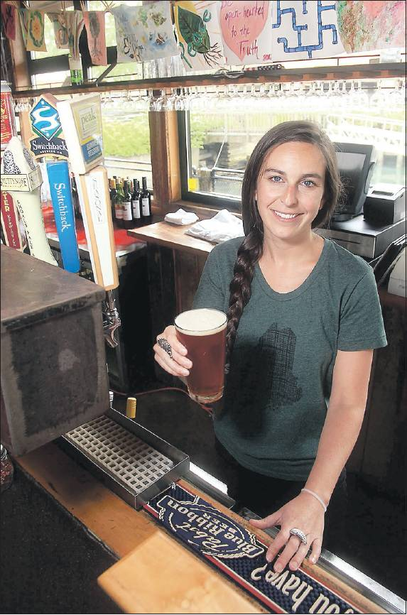 Katie Margo, a bartender at Flatbread Company in Portland, serves up a Baxter Amber Road
