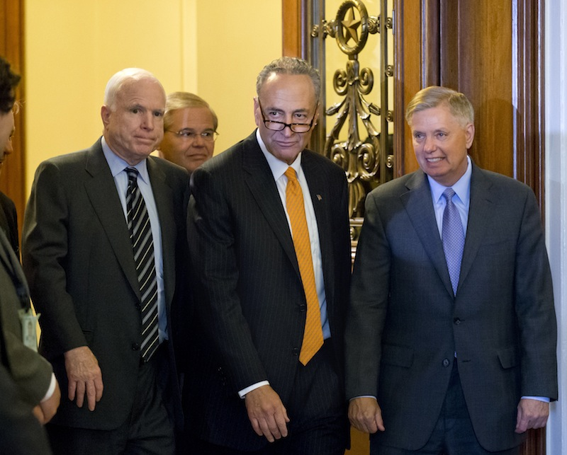 "Members of the bipartisan ""Gang of Eight"" who crafted the immigration reform bill, Sen. Chuck Schumer, D-N.Y., center, flanked by Sen. John McCain, R-Ariz., left, and Sen. Lindsey Graham, R-S.C., leave the floor after final passage in the Senate on Thursday. Sen. Robert Menendez, D-N.J., follows at rear."