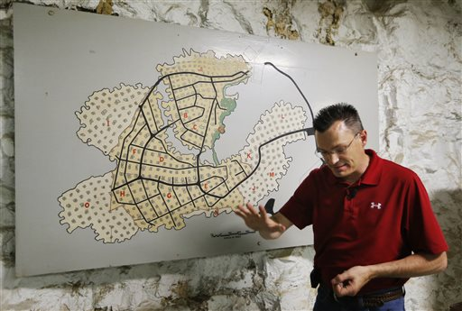 Coby Cullins stands next to a map of the Vivos Shelter and Resort during a tour of the facility in Atchison, Kan., on Tuesday.