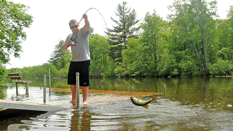 Ben Misner, 16, hauls in a 13-inch bass from a dock on Messalonskee Stream on North Street in Waterville on Thursday. Maine anglers are being asked to take photos of the striped bass they catch this summer in the name of science.