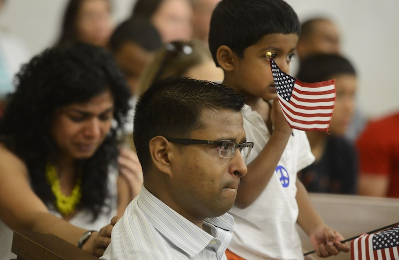 """Vrushali Deshmukh, left, and Ash Ingole, center, newly naturalized citizens from India, get choked up while listening to """"God Bless America"""" as Neil Ingole, 2, waves American flags during the naturalization ceremony at the York County Administrative Center on Thursday."""
