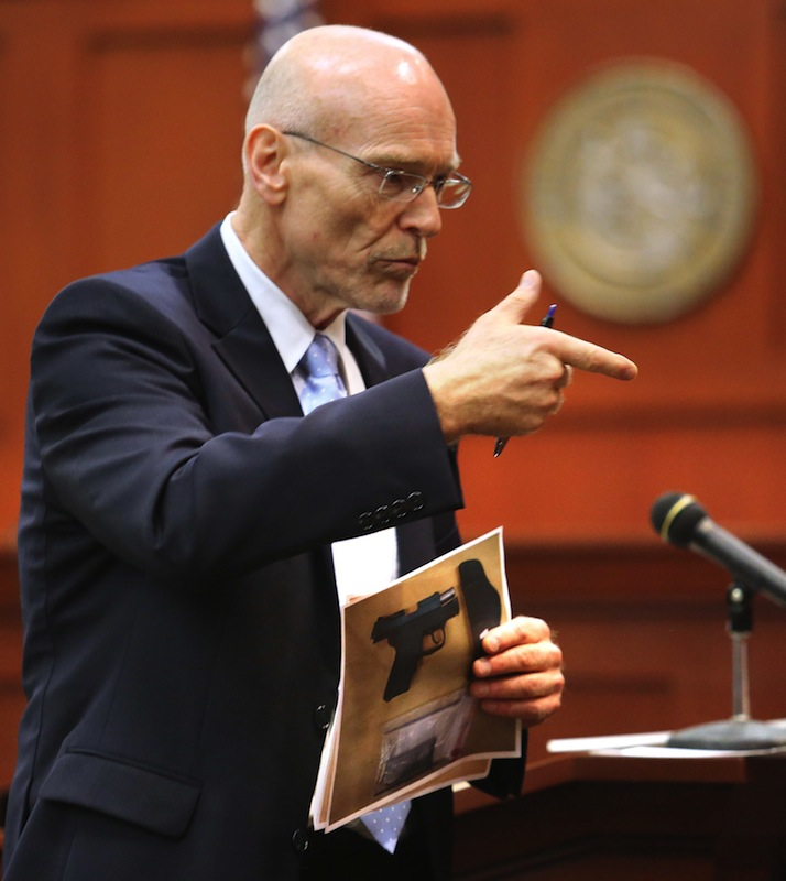 Don West, a defense attorney for George Zimmerman describes the shooting of Trayvon Martin to the jury while holding an evidence photo of a gun during opening statements in Zimmerman's trial in Seminole circuit court, in Sanford, Fla., Monday, June 24, 2013. Zimmerman has been charged with second-degree murder for the 2012 shooting death of Trayvon Martin. (AP Photo/Orlando Sentinel, Joe Burbank,Pool)