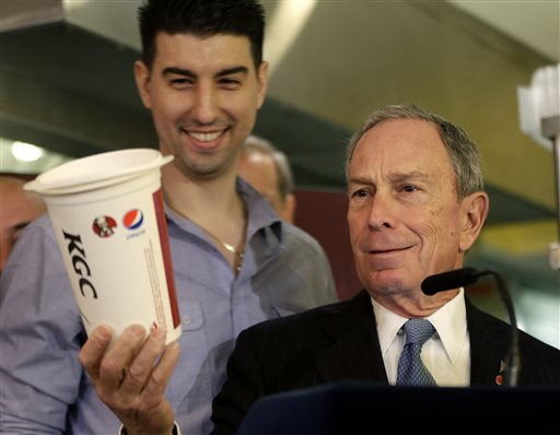 In this March 12, 2013, New York City Mayor Michael Bloomberg looks at a 64-ounce cup, as Lucky's Cafe owner Greg Anagnostopoulos, left, stands behind him, during a news conference at the cafe in New York. The mayors of New York, Los Angeles, Chicago and 15 other cities are reviving a push against letting government food vouchers be used to buy soda and other sugary drinks.