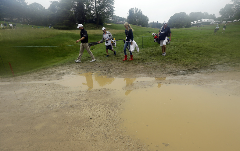 Martin Laird, left, of Scotland, walks near the fifth hole during the first round of the U.S. Open golf tournament at Merion Golf Club on Thursday in Ardmore, Pa. The course is drenched from a week of rain.