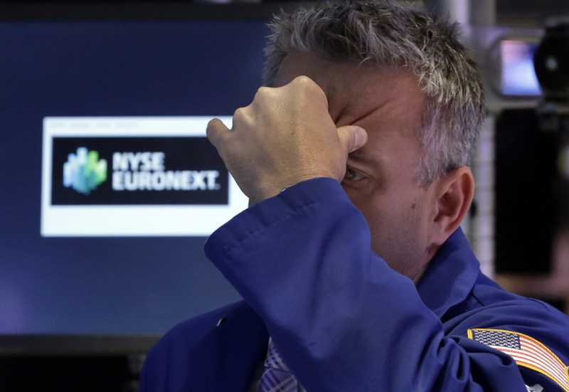 Specialist Christopher Culhane squeezes his forehead as he works on the floor of the New York Stock Exchange on Thursday.