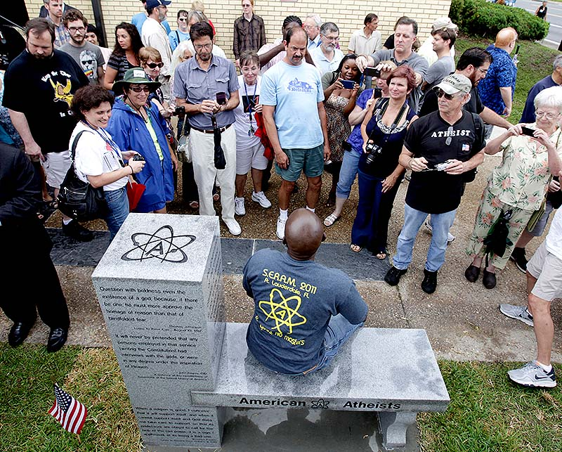 People gather around to sit and take photos during the unveiling of an Atheist monument outside the Bradford County Courthouse on Saturday in Stark, Fla. The New Jersey-based group American Atheists unveiled the 1,500-bound granite bench Saturday as a counter to the religious monument in what's called a free speech zone. Group leaders say they believe it's the first such atheist monument on government property.