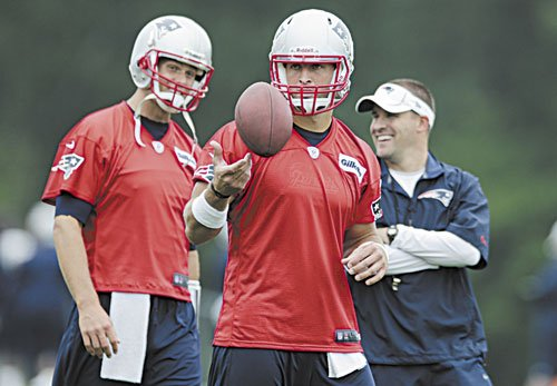 New England Patriots quarterback Tim Tebow, center, tosses the ball as Tom Brady, left, talks with offensive coordinator Josh McDaniels during practice in Foxborough, Mass.