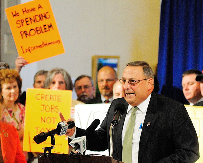 Gov. Paul LePage speaks during a budget rally on Thursday June 20, 2013 in the Hall of Flags at the State House in Augusta surrounded by 60 of his closest supporters. A day short of his deadline,LePage made good on long-standing threats to veto a bipartisan two-year state budget proposal unanimously endorsed by a legislative committee.