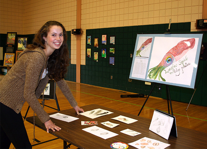 Bree Taylor, a Bonny Eagle High School student, sets up a display of her marine biology artwork for Visual and Performing Arts Night for SAD 6 students.
