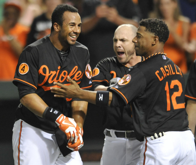 Baltimore's Chris Dickerson, left, celebrates with teammates Steve Pearce, center and Alexi Casilla, right, after hitting a three-run walkoff homer against Detroit.