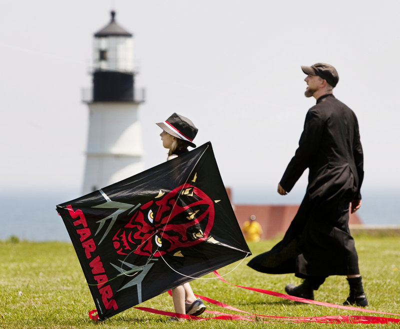 Aubrey Hutchinson, left, and Robert Brown walk near the Portland Head Light during the