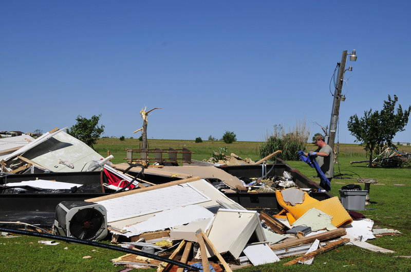 An El Reno, Okla., resident searches through the wreckage of a friend's mobile home after Friday's tornado, hoping to find undamaged belongings in El Reno on Saturday.