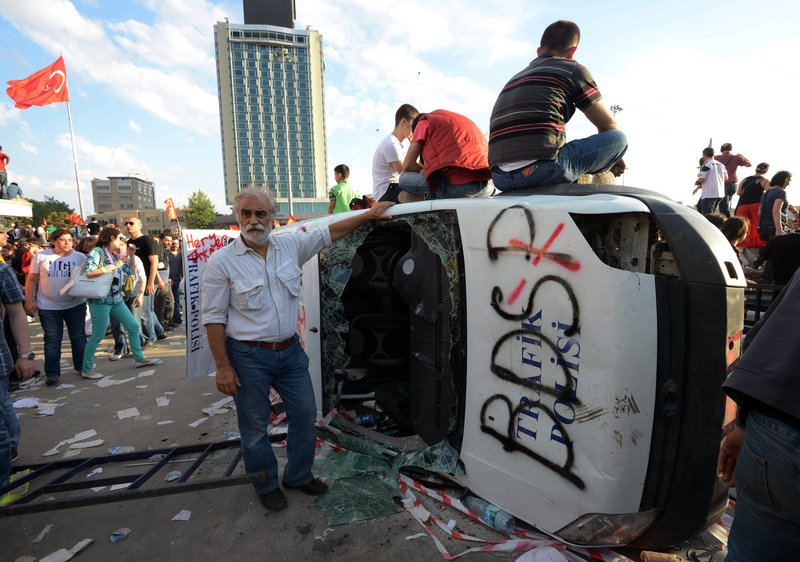 Turkish protesters climb onto a destroyed car Saturday at Istanbul's Taksim Square. Police retreated from the square, removing barricades and allowing in thousands of protesters.