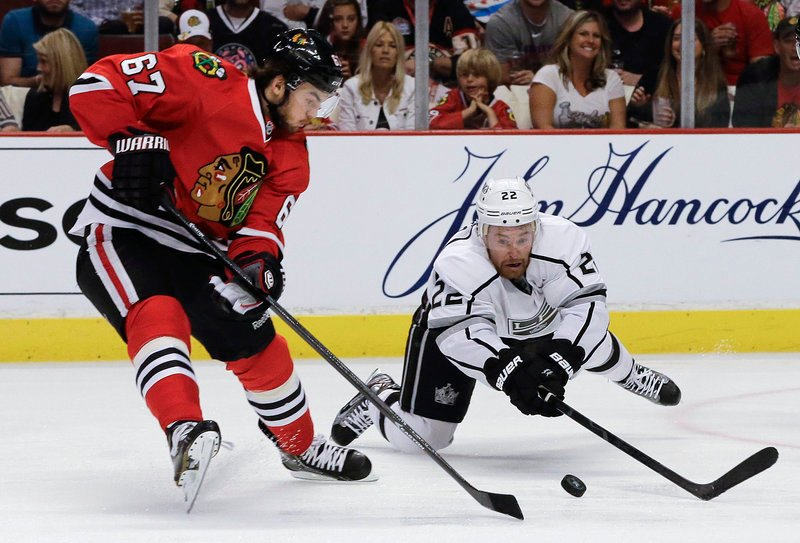 Rival forwards Michael Frolik (67) of the Chicago Blackhawks and Trevor Lewis of the Los Angeles Kings scrap for a loose puck during Saturday's semifinal opener, won by Chicago.