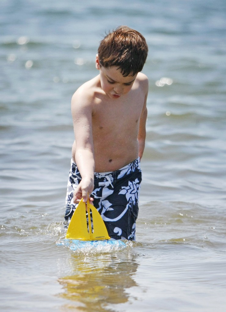 Abe Sullivan, 9, of Portland gives his toy sailboat a try Sunday at Kettle Cove in Cape Elizabeth. Abe was visiting the beach with his mother, Julie, and his sister, Sara, 8.