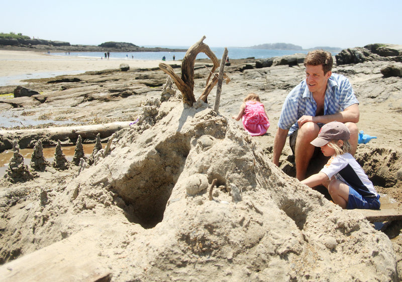 Jed Rauscher and his daughter, Anna, 6, put the finishing touches on their first sand castle of the year, which they built Sunday with help from Anna's sister, Maci, 4, behind her father, and several other children at Kettle Cove in Cape Elizabeth.