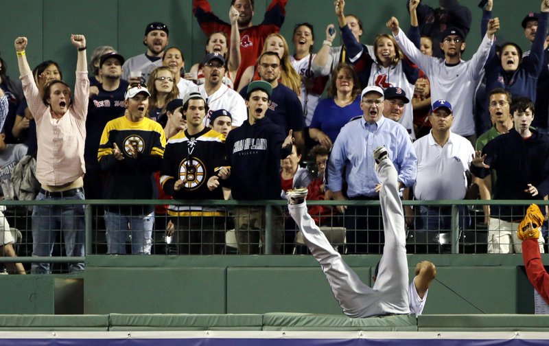 The Rangers' Nelson Cruz treats the Fenway fans to a major-league effort, as he tumbles headlong over the right-field fence in an attempt to catch a homer by Boston's Mike Carp.
