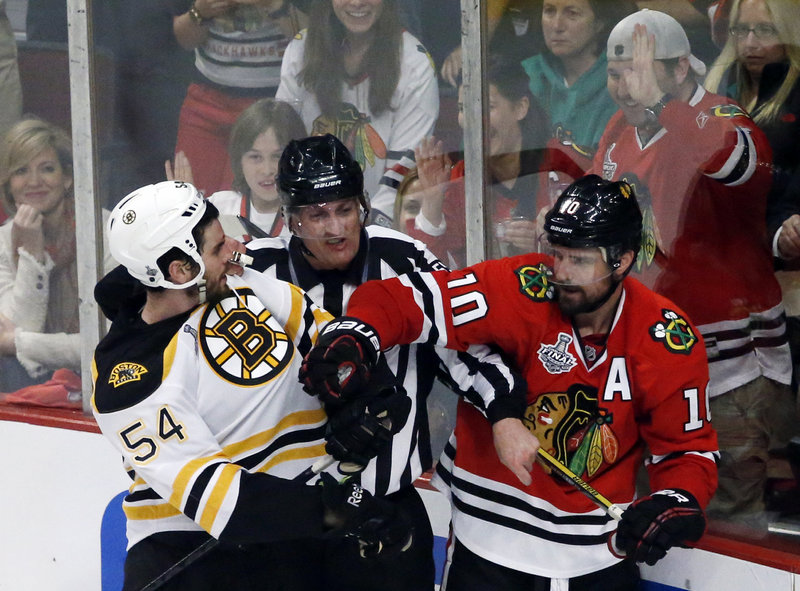 An official tries to break up a fight as Bruins defenseman Adam McQuaid goes after Chicago's Patrick Sharp Wednesday. Chicago won Game 1 of the Stanley Cup finals, 4-3.