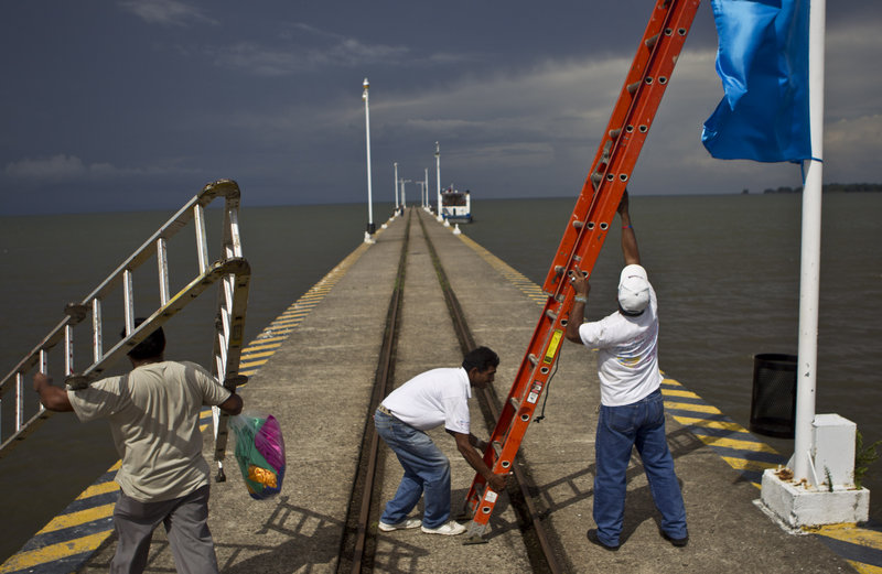 Workers position a ladder to hang a banner on a wharf in Granada surrounded by Lake Nicaragua, which would almost certainly be crossed by the planned canal.