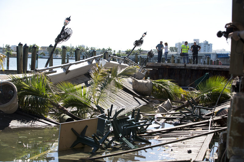 Officials begin their inspection of the outdoor deck that collapsed at Shuckers Bar & Grill. The packed outdoor deck behind the popular Miami-area sports bar partially collapsed during the NBA Finals on Thursday night, sending dozens of patrons into Biscayne Bay.