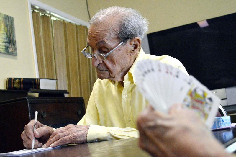 Joe Tuzzo keeps score while playing bridge at the Claire Teague Senior Center. Tuzzo is considered the man to beat when it comes to the monthly wordsmith competition at the center.