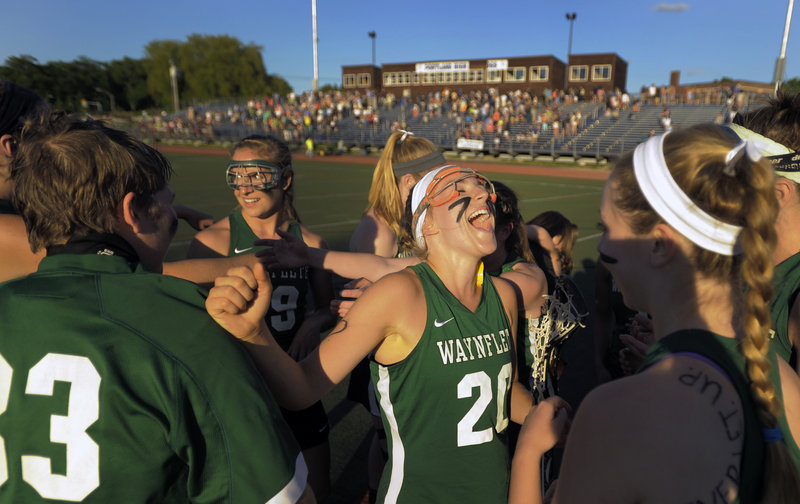 Cat Johnson rejoices with her Waynflete teammates after the Flyers capped an unbeaten season with a 7-4 win over Yarmouth in the Class B lacrosse final.