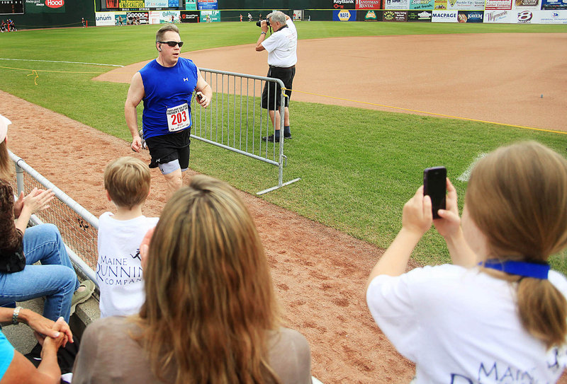 Courtney Jackson, right, snaps a photo of her dad, Brian, as he finishes the race. Courtney, 8, was there with her mom, Cathy, and twin sister, Kayla.