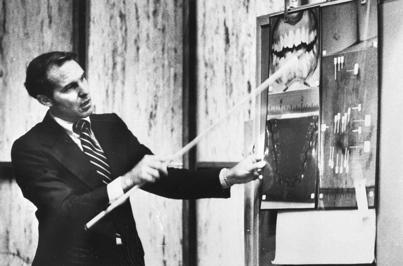 "Forensic odontologist Dr. Richard Souviron points to a photo of Ted Bundy's teeth during Bundy's 1979 murder trial in Miami. Souviron, who is considered the founding father of bite-mark forensics, argues there's a ""real need for bite marks in our criminal justice system."""