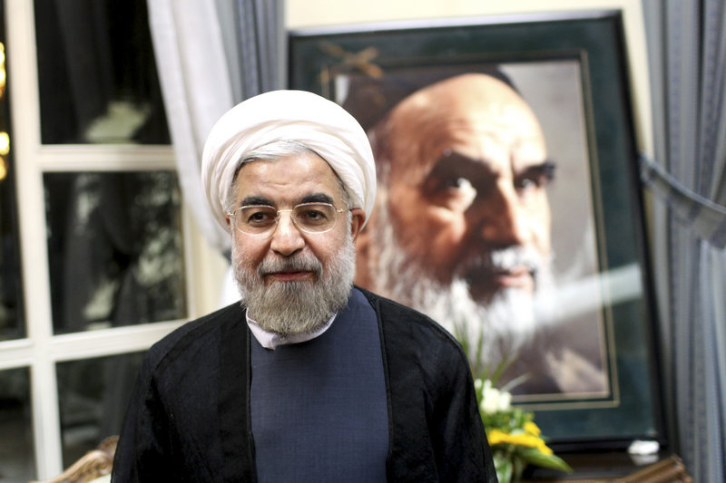 Hasan Rowhani, Iran's newly elected president, stands in front of a portrait of the late Ayatollah Khomeini at a shrine outside Tehran on Sunday. Many saw his win as a slap to the ruling clerics, sending a message that they cannot keep the opposition bottled up.