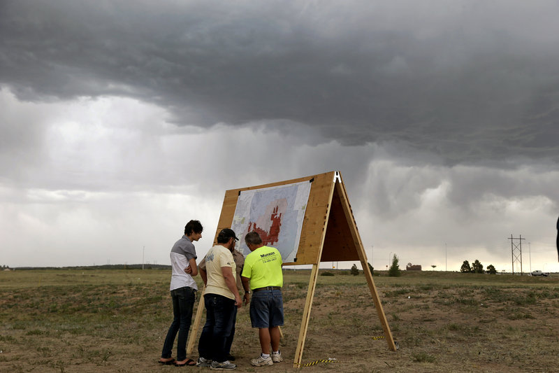 Residents look at a map detailing progress of the Black Forest wildfire Sunday in Colorado Springs, Colo. Fire crews were putting out hot spots Sunday in the Black Forest.