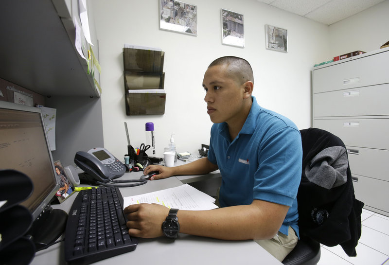 Jorge Tume works on a computer at a concrete company in Miami. Tume's parents brought him and his younger brother to the U.S. from Peru on tourist visas when they were young.