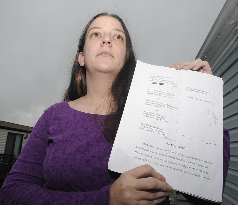 Natalie Gunshannon holds a copy of a lawsuit filed against the owners of a McDonald's franchise.