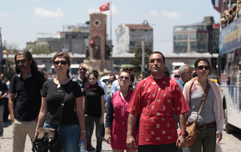 Protesters stand in a silent protest Tuesday at Taksim Square in Istanbul, Turkey. After weeks of unrest, Turkish protesters have found a new form of resistance: standing still and silent.