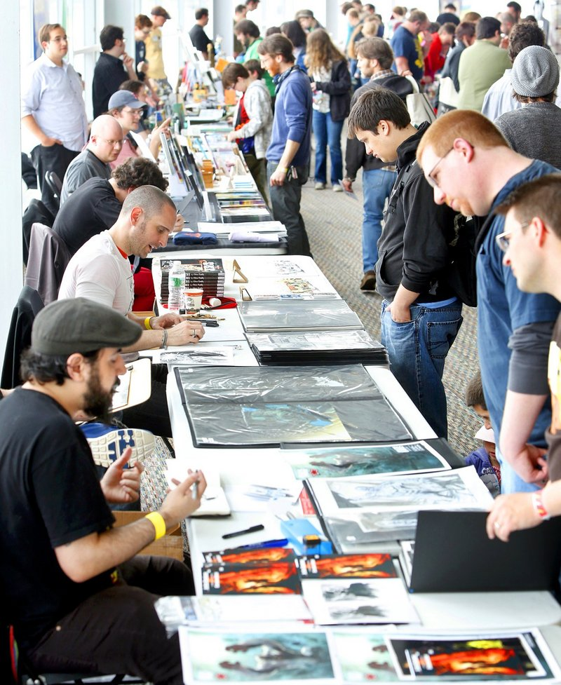 Illustrators Christian Dibari, bottom left, and Sean Murphy above left, discuss their art at the Maine Comics Arts Festival in Portland in May. Events like comic book conventions give