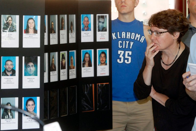 Springfield, Vt., resident Susan White looks over booking photos displayed Wednesday as state police announced the arrests of 33 people in a drug sweep. An increase in heroin traffic statewide prompted this operation and an earlier one that resulted in 47 arrests.
