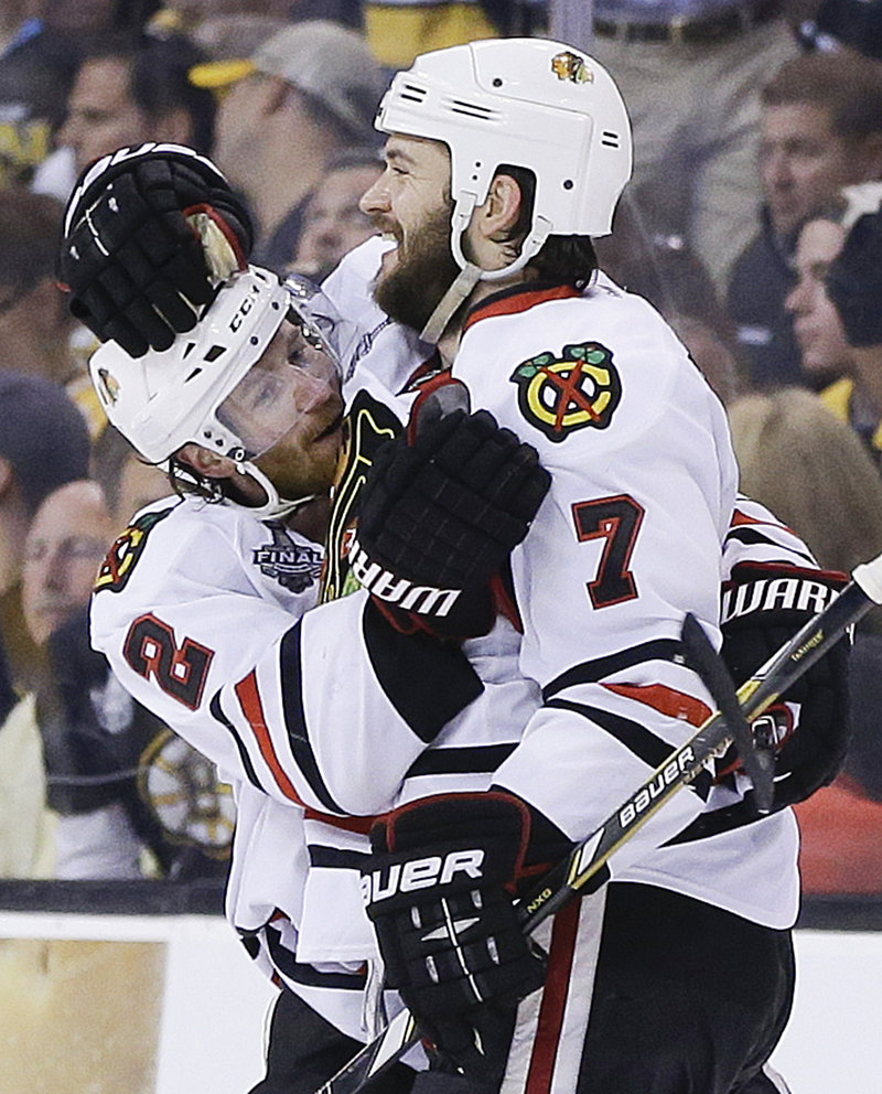 The Blackhawks get to celebrate again in OT as Brent Seabrook, right, embraces Duncan Keith after scoring at 9:51 of overtime Wednesday night at Boston. The Blackhawks' 6-5 win evens the Stanley Cup finals, 2-2. Chicago won Game 1 in triple overtime.