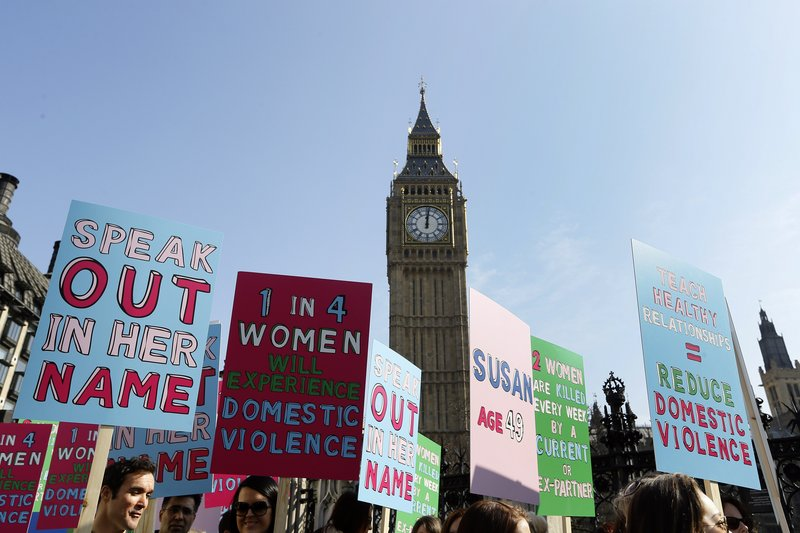 People hold banners during a demonstration against domestic violence near Big Ben in London in March, as part of events leading up to International Women's Day.