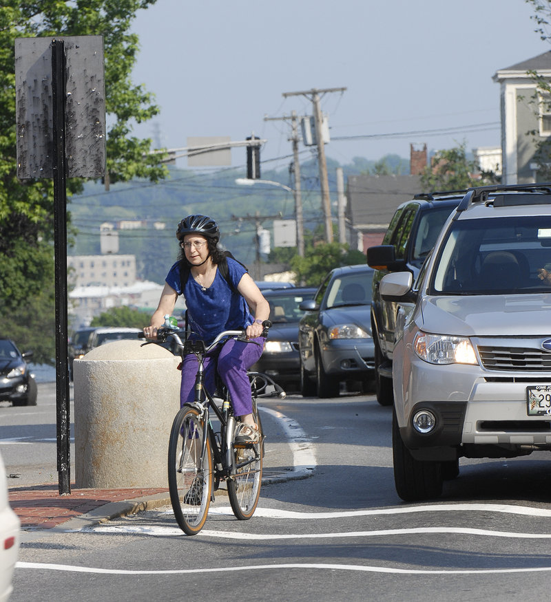 "A bicycle commuter navigates traffic in Portland in 2008. A reader says, ""I am a driver and a cyclist, and when in my car I see much more bad, rude and dangerous driving from other motorists than I ever do from cyclists."""